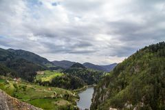 Zaovine valley and lake seen from the top of a cliff, with some mountain village houses seen, surrounded by pine trees,. Picture of a mountain valley seen from a royalty free stock photography