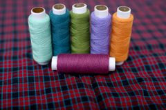 Picture of multi colored sewing thread on the cloth stock photos