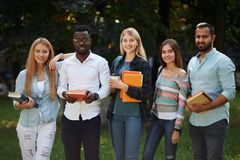 Picture of multiethnic group of graduates students standing outdoors. Picture of multiethnic group of young happy adult students standing outdoors in campus royalty free stock images