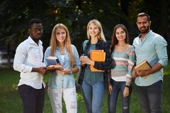 Picture of multiethnic group of graduates students standing outdoors. Picture of multiethnic group of young happy adult students standing outdoors in campus royalty free stock image