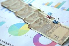 Picture of multiple new pack of Indian 10 Rupee notes with chart paper. Isolated on wooden background royalty free stock image