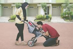 Muslim family kissing their baby in the stroller. Picture of Muslim family kissing their cute baby in the stroller while standing in the front of their house Stock Image
