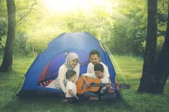 Muslim family playing a guitar in the camping tent. Picture of Muslim family singing and playing a guitar in a tent while camping in the forest at morning time stock photos