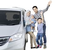 Muslim family waving hands on studio. Picture of Muslim family standing near their car while waving hands at the camera, isolated on white background Royalty Free Stock Photo