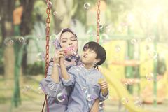 Muslim woman blows soap bubbles with her son. Picture of Muslim women blowing soap bubbles while sitting with her son on the swing. Shot in the playground Royalty Free Stock Photo