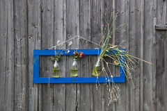 Picture from nature on the wooden wall. Modern frame on the old wooden wall, with flowers inside of three bottles Stock Photos