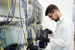 Picture of network technician testing modems in factory. Picture of network technician engineer testing modems in factory royalty free stock photography
