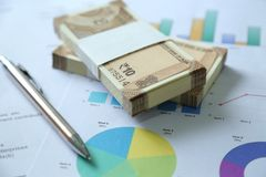 Picture of new Indian Currency Rupees from pack with chart paper and pen. Isolated on wooden background stock photo