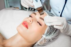 Picture of nice beautician doing oxygen therapy for young woman laying. Down with closed eyes in a beauty salon royalty free stock photo