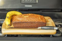 Fresh Baked Banana Bread. Picture o Fresh baked Banana bread displayed on top of a stove.  Banana bread is sitting on top of a wooden cutting board Stock Photography