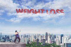 Obese man pulling text of weight loss. Picture of obese man standing on the rooftop while pulling text of weight loss on the sky Royalty Free Stock Photography