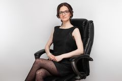 Picture Of Beautiful Woman In Black Dress Sitting In The Armchair Stock Photo