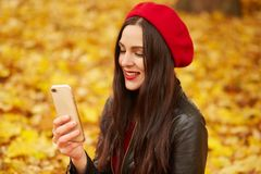 Free Picture Of Young Woman Making Selfie Or Having Video Call In Autumn Park. Beautiful Girl Dresses Redberet And Leather Jacket Takes Stock Images - 160706854