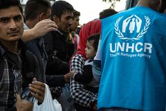 Worker of the UNHCR, the United Nations Agency for refugees, standing in front of a crowd of refugees, including a baby royalty free stock photography