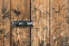 Picture of old brown colored wooden door locked with a padlock.  Stock Photo