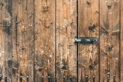 Picture of old brown colored wooden door locked with a padlock.  Stock Photography