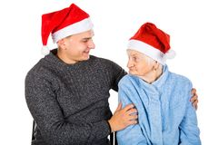 Christmas gift for a beautiful grandmother. Picture of an old lady celebrating Christmas with her grandson stock photo