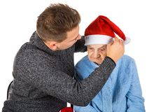 Christmas gift for a beautiful grandmother. Picture of an old lady celebrating Christmas with her grandson stock photos