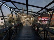 Old lady crossing a metal cage peatonal bridge royalty free stock image