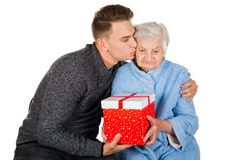 Gift for a beautiful grandmother. Picture of an old lady receiving birthday gifts from her grandson stock photo
