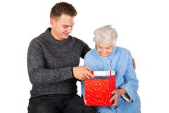 Gift for a beautiful grandmother. Picture of an old lady receiving birthday gifts from her grandson royalty free stock photos