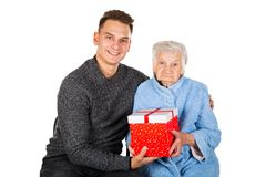 Gift for a beautiful grandmother. Picture of an old lady receiving birthday gifts from her grandson stock image