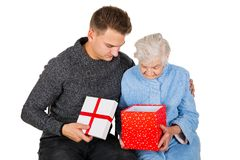 Gift for a beautiful grandmother. Picture of an old lady receiving birthday gifts from her grandson royalty free stock image