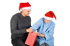 Christmas gift for a beautiful grandmother. Picture of an old lady receiving Christmas gifts from her grandson stock image
