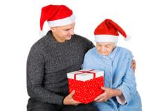 Christmas gift for a beautiful grandmother. Picture of an old lady receiving Christmas gifts from her grandson stock photography
