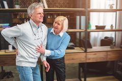 A picture of old man keeping his hand on the back. He has a pain. A picture of old men keeping his hand on the back. He has a pain in the spine. The women wants Royalty Free Stock Photography