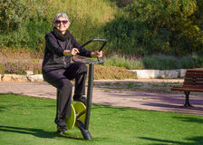 Picture of old woman tries out spinning cycle trainer Royalty Free Stock Photos
