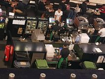 Picture of an open coffee shop with customers ordering their drink and baristas in action. stock photography