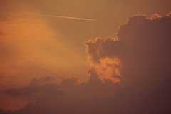 Picture Of Orange Sky With Warm Clouds And A Plane, Shot During Golden Hour Image Of The Evening Sky With Contrails Of A Plane stock photography