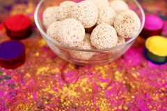 Picture of organic holi color with cholai ke ladoo in the glass bowl. Isolated on the colorful background stock images