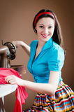 Picture of sewing beautiful brunette young lady pinup girl with red lips for blue shirt & ribbon on her head happy smiling. Image of pinup pretty girl with red Stock Image