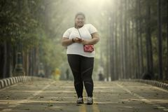 Overweight woman with smartphone in the road Royalty Free Stock Photography