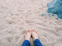 Picture of a pair of asian lady& x27;s feet laid down on the sand beach and sit near a rock. A girl laid down and relax on the beach with bare feet stock image