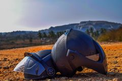 Pair of black helmet kept under the hot sunlight on a rough road stock image