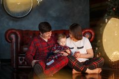 Picture of parents sitting together with their child on the floor. They are looking at him. Kid is playing on th phone. Dad is holding child on nap stock photography