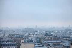 Aerial view of Paris, capital city of France, during a cold winter afternoon, with clouds and fog generated by pollution. royalty free stock photography