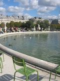 A part of the tuileries in Paris. A picture of a part of the beautiful tuileries in Paris with the wellknown green chairs, the fountain and the historic royalty free stock image