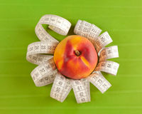 Picture of a peach and tape measure Royalty Free Stock Image