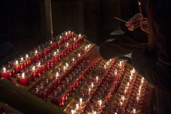 People lighting candles in the Notre Dame cathedral in Paris, France. Burning a candle is a usual practice in Catholicism. Picture of people lighting candles in stock photography