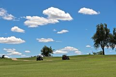 Picture Perfect Golf Day. Clouds floating above the golf course, with golf carts on the cart path Stock Images