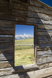 Picture Perfect Grand Tetons. The Grand Teton mountain range in Western Wyoming is framed in the window opening of an old, weathered, log cabin royalty free stock image