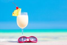 Picture of pina colada and sunglasses on tropical Royalty Free Stock Photos