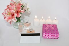 Picture of a pink luxury gift box with a bouquet of beautiful Alstroemeria flowers, a romantic candle, perfume and a credit card. Dressing table with women`s stock images