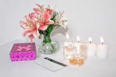 Picture of a pink luxury gift box with a bouquet of beautiful Alstroemeria flowers, a romantic candle, perfume and a credit card. Dressing table with women`s stock image