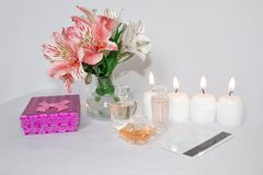 Picture of a pink luxury gift box with a bouquet of beautiful Alstroemeria flowers, a romantic candle, perfume and a credit card. royalty free stock photo