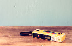 Picture of an plastic camera on a wooden table. retro filter Stock Image